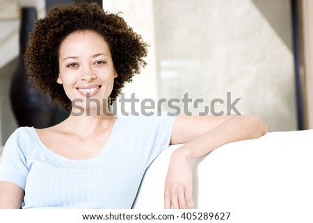 Woman relaxing on a sofa, smiling - stock photo