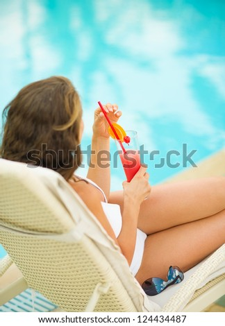 Woman relaxing on chaise-longue with cocktail. Rear view - stock photo