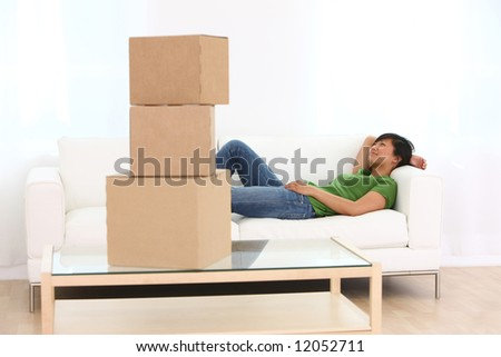 Woman relaxing on couch with boxes in foreground - stock photo