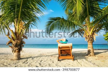 Woman relaxing on deckchair, tropical beach of Indian ocean, Maldives - stock photo