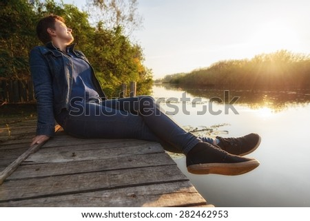 Woman relaxing on jetty at evening hours - stock photo
