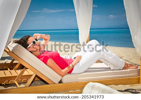 Woman relaxing on luxury bed at the sea beach. Greece. - stock photo