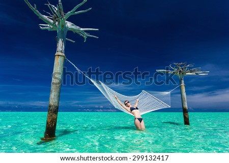Woman relaxing on over-water hammock in the middle of tropical lagoon, Maldives - stock photo