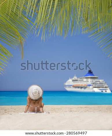 Woman relaxing on the beach  watching a cruiseship passing by - stock photo