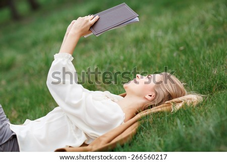 Woman relaxing outdoors looking happy and smiling - stock photo