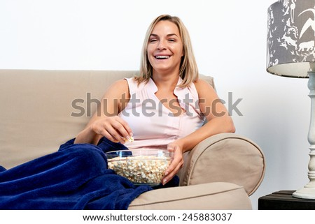 woman relaxing with a bowl of popcorn while watching t.v. on sofa couch - stock photo