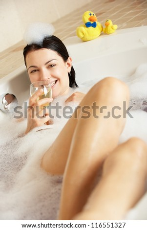 Woman Relaxing With Glass Of Wine In Bubble Filled Bath - stock photo