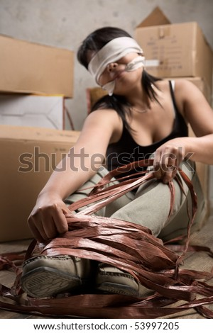 Woman release the rope which tied her up. Low key setting - stock photo