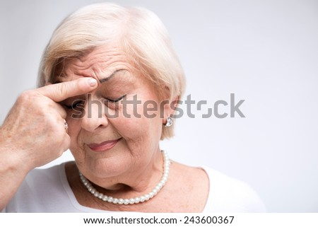 Woman remembering something. Closeup portrait of elderly woman touching her nose trying to remember something with her eyes closed while standing against white background - stock photo