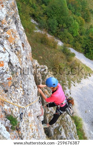 Woman removes protection gear while hanging on the rope high above ground - stock photo