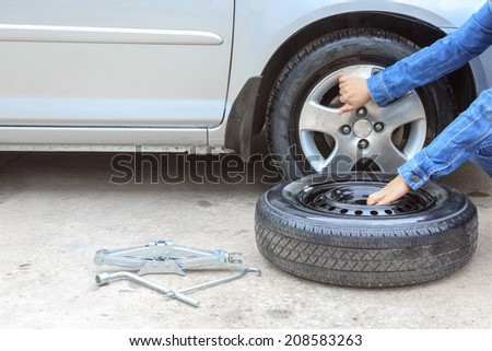 woman removing a wheel  car on the roadside - stock photo