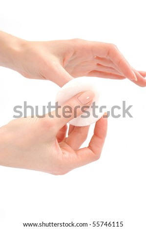Woman removing lacquer from manicured nails with white cotton pad - stock photo