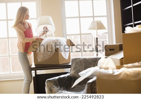 Woman removing lamp from moving box at new house - stock photo