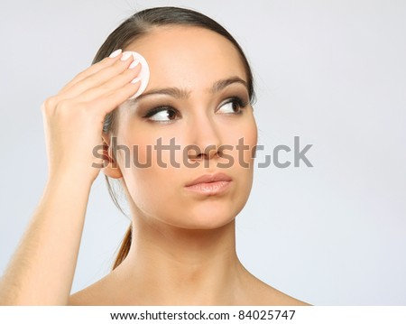 Woman removing makeup with cleansing pads isolated on grey background - stock photo