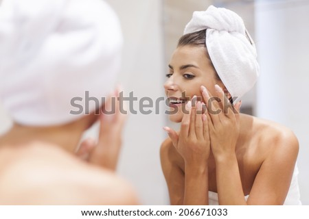 Woman removing pimple from her face  - stock photo