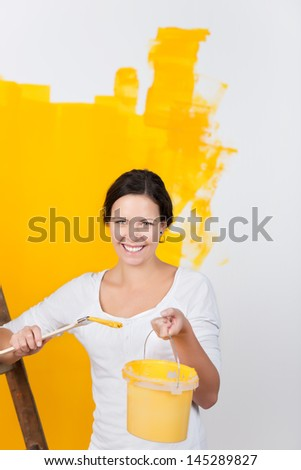 Woman renovating her house standing smiling at the camera holding up a bucket of paint and brush in front of a half painted wall in bright yellow paint - stock photo
