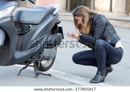 woman repairs a scooter - stock photo