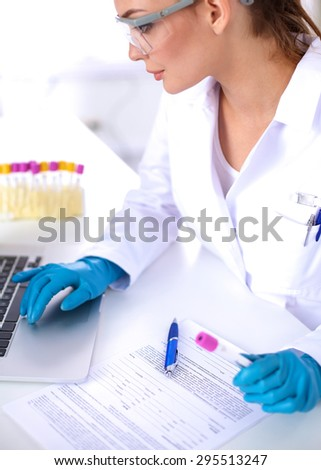 Woman researcher is surrounded by medical vials and flasks, isolated on white - stock photo