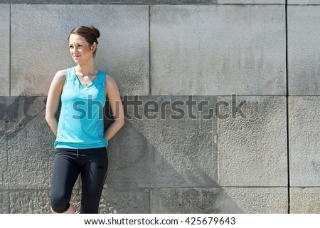 Woman resting after run by the wall urban.  - stock photo