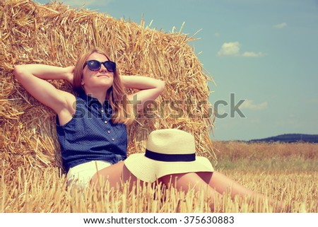 Woman resting on a bale of straw on the field - stock photo