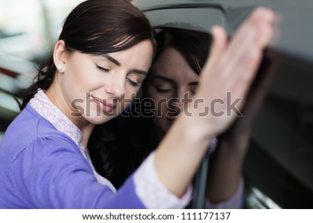 Woman resting on a car in a car dealership - stock photo