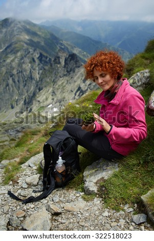 Woman resting on a mountain trail in a summer day - stock photo