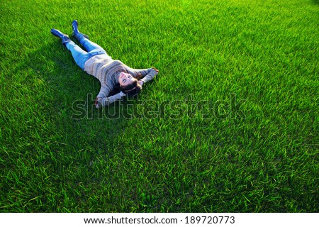Woman resting on green grass - stock photo