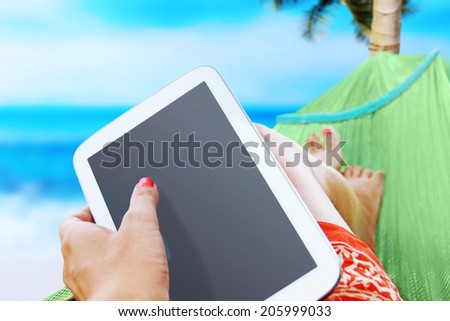 woman resting on the sea with a white tablet - stock photo