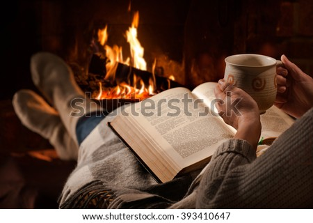 Woman resting with cup of hot drink and book near fireplace - stock photo