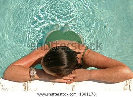 Woman rests by the side of the pool - stock photo