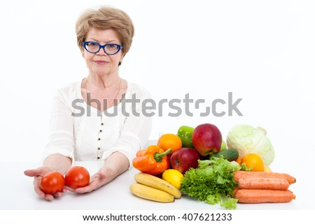 Woman retirement age with two tomatoes in hands sitting near fresh fruit and vegetables, white background - stock photo