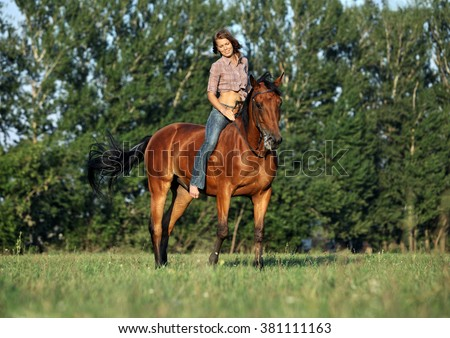Woman rider on back of her horse in evening trail - stock photo