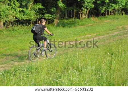 woman riding a bike on a road in forest. it has a bit motion blur - stock photo
