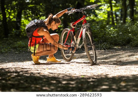 Woman riding a mountain bike in the forest.She  repairing her bike. - stock photo