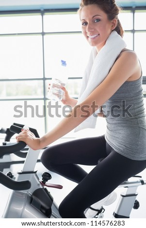 Woman riding an exercise bike and drinking a bottle of water - stock photo