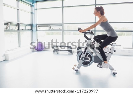 Woman riding an exercise bike in gym - stock photo