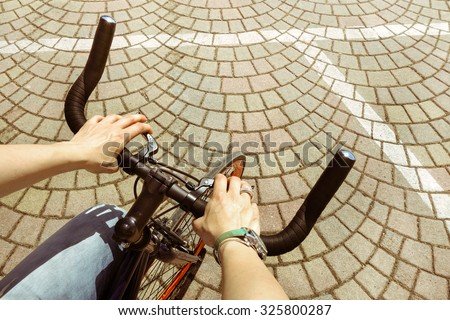 Woman riding  bicycle in central city square - Woman hands on modern sport bike -  Young girl cycling in urban street - Green concept of alternative transport preserving and saving environment matters - stock photo