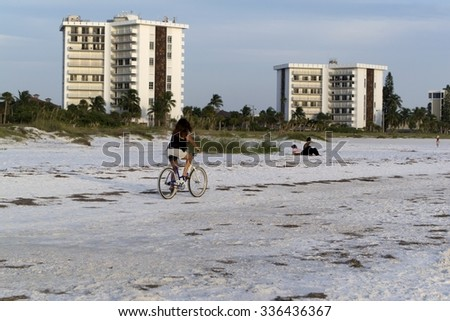 Woman riding bicycle on beach - stock photo