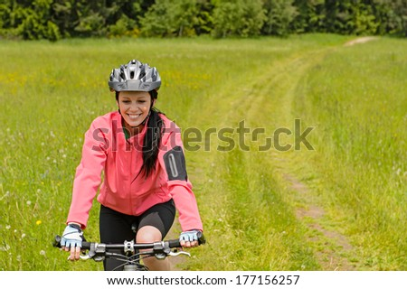 Woman riding bicycle on countryside path through meadow smiling - stock photo