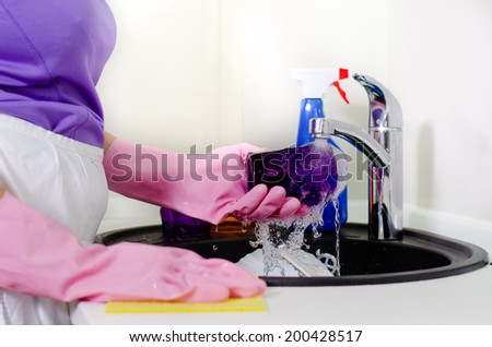 Woman rinsing plates under running water the tap as she does the washing up after a meal, close up of her gloved hands - stock photo