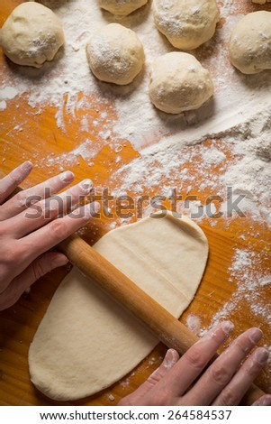 Woman rolling dough with rolling pin on kitchen counter - stock photo