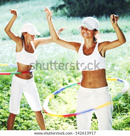 woman rotates hula hoop on nature background - stock photo