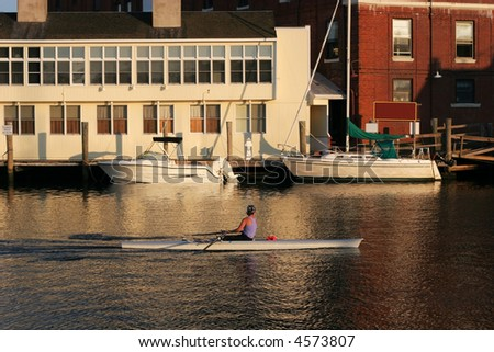 woman rowing in Mystic River, Mystic, CT - stock photo