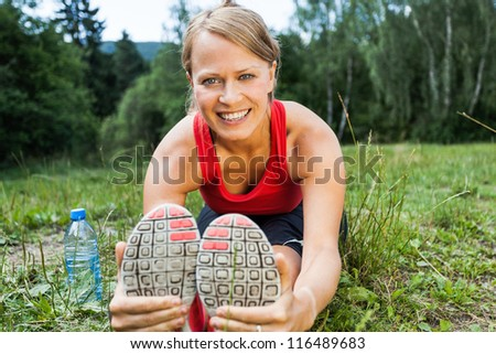Woman runner exercising and stretching, summer nature outdoors. Female athlete working out on grass, activity and exercise - stock photo