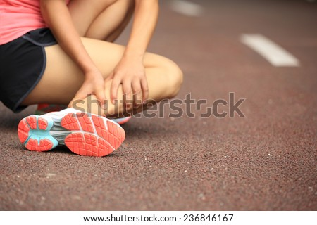 woman runner hold her twisted ankle  - stock photo