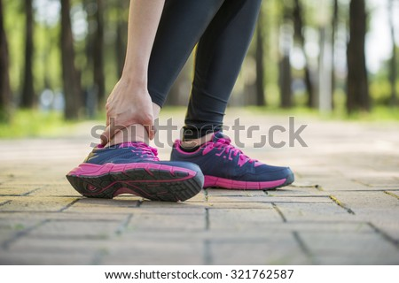 woman runner hold twisted ankle Pain ,Human Leg Cramp - stock photo