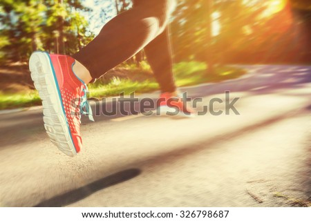 Woman runner jogging down an outdoor trail at sunset - stock photo