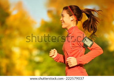 Woman runner running in fall autumn forest listening to music on smartphone using earphones. Female fitness girl jogging on path in amazing fall foliage landscape nature outside. - stock photo