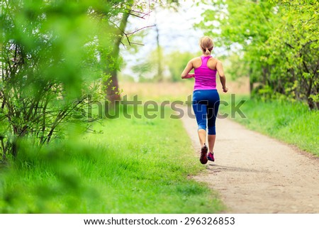 Woman runner running with dog in park on country road, healthy lifestyle and training working out outdoors, exercising in bright colorful environment. Inspirational and motivational concept. - stock photo