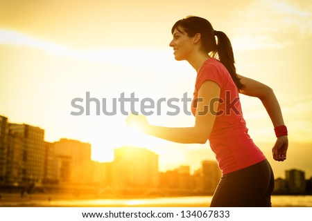 Woman running and exercising on beautiful golden summer sunset background on city beach. Female athlete fitness girl training. copy space. - stock photo